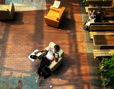 Student lounging in a chair in the UC Atrium