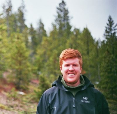 Sawyer Connelly smiles at the camera while standing in a forest. He wears a black Arcteryx jacket