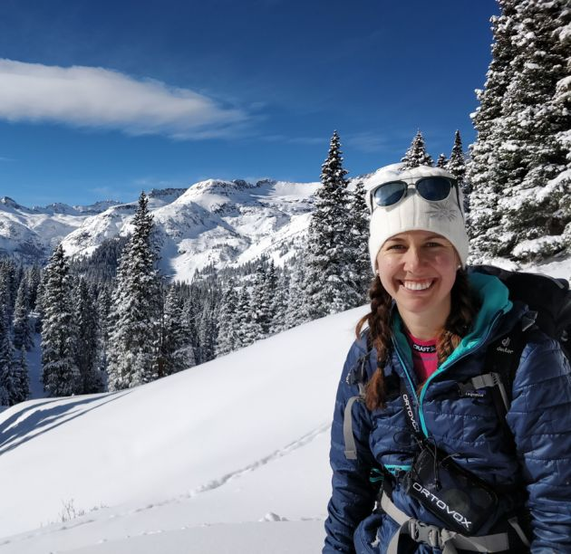 Amy Katz smiles at the camera while outside in the snow-covered mountains. She is wearing a white knit hat. A large, snow-covered peak looms in the background.