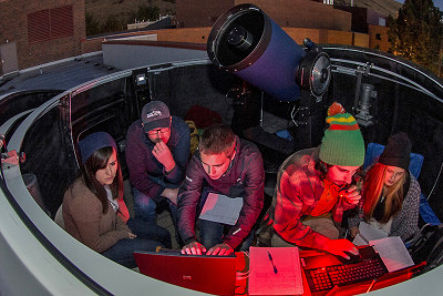 University of Montana astronomy students work on computer under the night sky