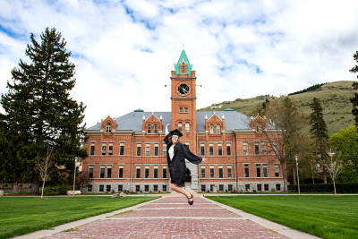 A picture of a female student jumping in front of Main Hall in her graduation outfit.