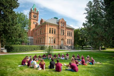 A group of students wearing maroon sits in a circle on the grass with Main Hall in the background
