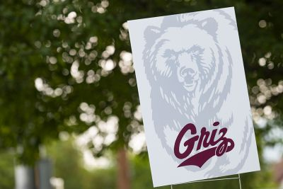 A sign with a Grizzly bear sits in front of tree in town