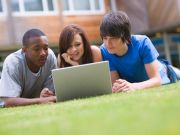 3 people lying on the grass looking at a laptop