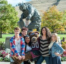 group of students with Monte in front of bear statue