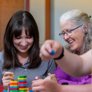 A student and faculty member using math manipulatives