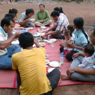 outdoor picnic with 10 people sitting in a circle on a blanket