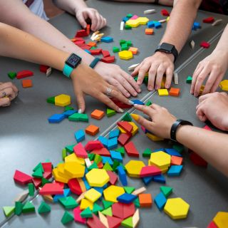 Several hands reaching for colored blocks on a table