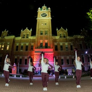 Members of the UM Dance Team perform in front of Main Hall at night during the Homecoming Pep Rally.