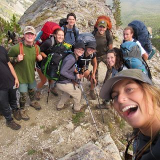 Students stand on a mountain peak and smile for a selfie taken by a member of the Freshman Wilderness Experience.