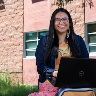 A student smiles at the camera while sitting outside the Payne Family Native American Center. There is a laptop on her lap.