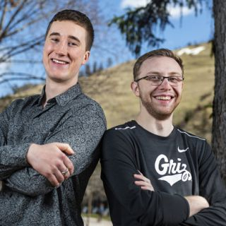 Recent UM graduates Noah Grabe, left, and Taylor Gregory, right, stand back-to-back on campus.