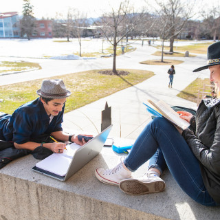 Two students study in the sunshine on the steps of Rankin