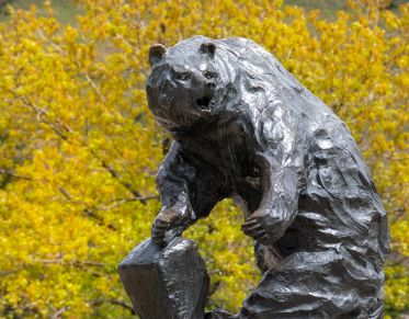 Griz statue with trees and flowers