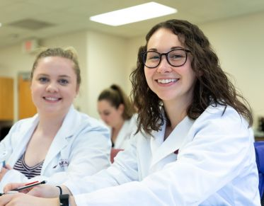 Two pharmacy students in lab coats smiling from their classroom seats
