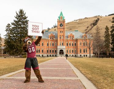 """Monte the mascot holding a sign in front of Main Hall that reads: """"YOU GOT THIS."""""""