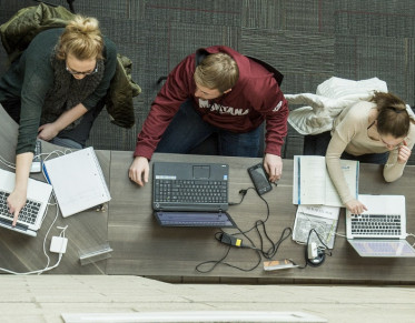 Three students each using laptops and collaborating