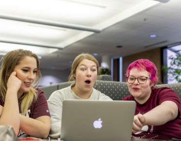 Three students using a laptop looking surprised