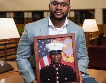 a veteran holding a photo of himself in uniform