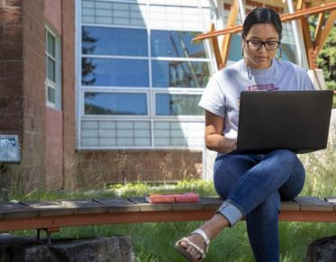 someone sitting on campus typing on a laptop