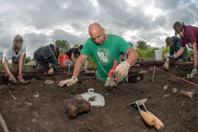 A man in a green shirt uses a brush to move dirt at an archaeological dig site. Other diggers are in the background.