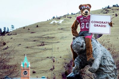Monte the mascot sits on top of the Grizzly Bear Statue while holding a sign that reads Congrats, Grads! Mounti Sentinel in the background