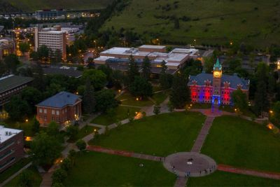 UM's Oval with Main Hall lit in red and yellow as seen from a drone camera