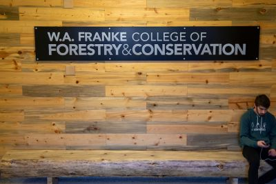 a student sits under a sign that reads W.A. Franke College of Forestry and Conservation