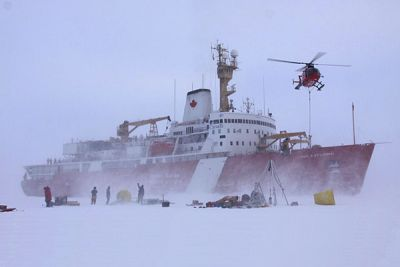 Crew members deploy equipment onto the ice from a Canadian icebreaker.