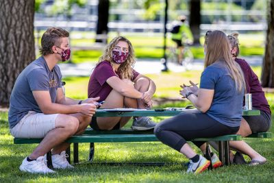 UM students talk at a picnic table on the Oval