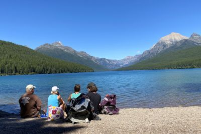 A family enjoys a lake view in Glacier National Park.