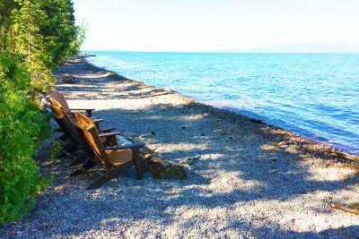 A picture of lawn chairs on a new rocky beach at Flathead Lake