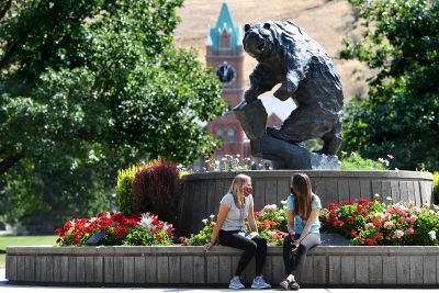 Students with masks chat by the Grizzly Bear statue.