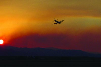 Photo of plane flying over forest fire.