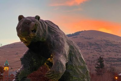 A December sun rises over UM's Grizzly Bear statue.