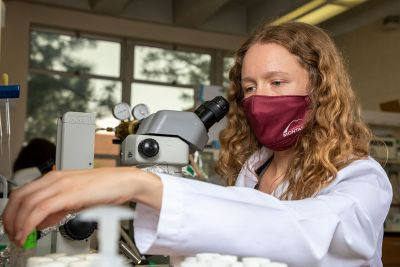 Lab technician Ashley Bielawski works with a microscope sporting a UM mask.