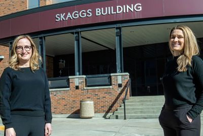 Pharmacy faculty members Erica Woodahl (left) and Hayley Blackburn pose for a picture before UM's Skaggs Building.
