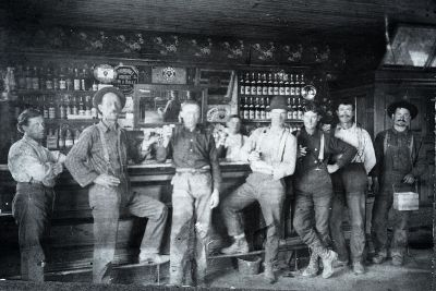 This is a very old photo of seven men standing in front of a saloon bar with bottles in the background
