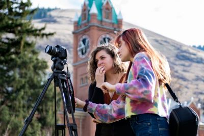 Two female journalism students work with a camera near Main Hall.