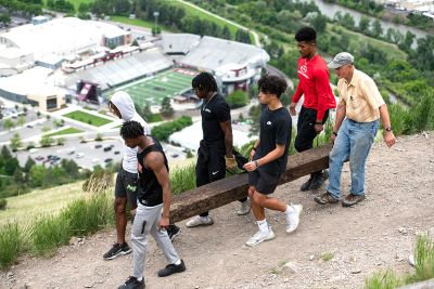 M Trail project leader Dr. Steve Gaskill carries a railroad tie with Griz football players earlier this summer.