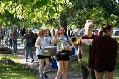 A row of students and parents carrying items walk down the sidewalk under trees