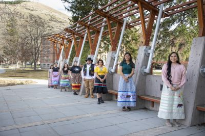 Student members of Kyiyo lean against the Payne Family Native American Center