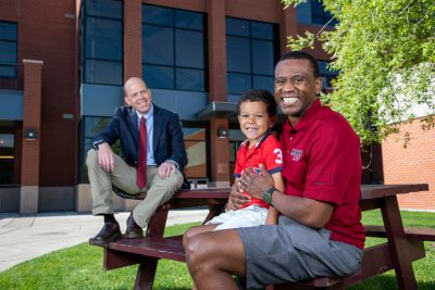 A law professor sits on a picnic table with a law student and his son