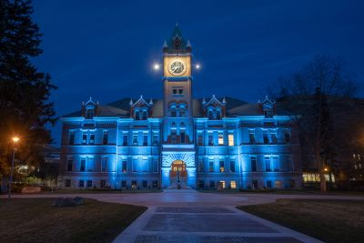 A view from the University of Montana Oval of Main Hall lit up in teal at night