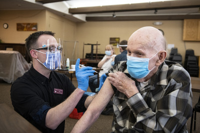 A UM pharmacist vaccinating an elderly man.