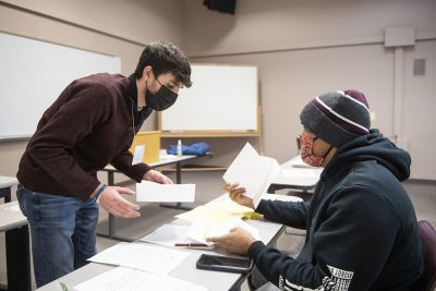A UM student hands a paper across a table to a member of the public.