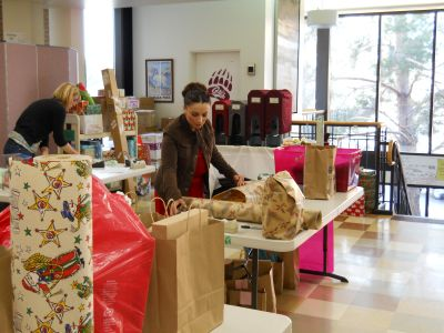 Volunteers help wrap presents for the Adopt-A-Family and Adopt-A-Veteran programs