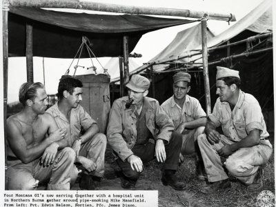 Four GI's from Montana in 1944 Northern Burma gather around a pipe smoking Mike Mansfield