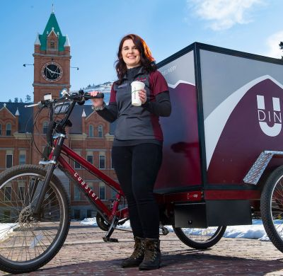 Katie Helms in front of the pedal powered UM Dining cart