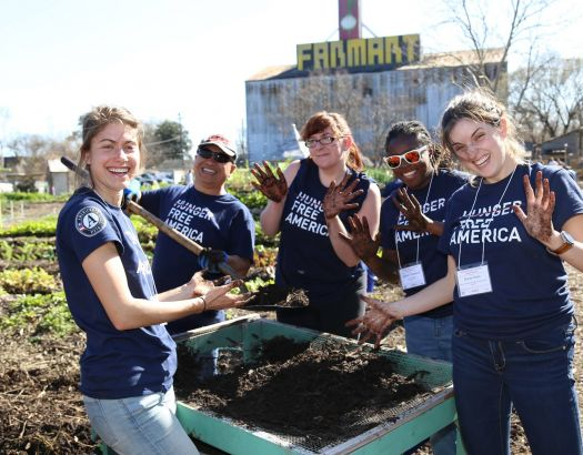 four americorps volunteers stand around a soil sifter in a garden